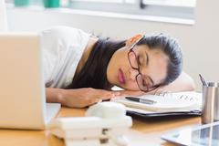 Businesswoman sleeping on desk - stock photo