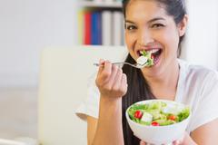 Stock Photo of Happy businesswoman eating healthy salad