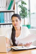 Stock Photo of Businesswoman holding documents while using laptop