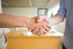 Stock Photo of Business people shaking hands in office
