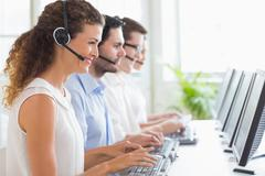 Customer service representatives working at desk Stock Photos