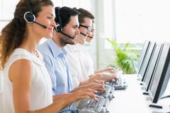 Call center operators working at desk - stock photo