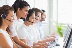 Manager assisting her staffs in call center - stock photo