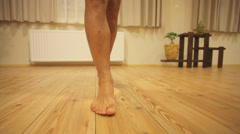 Man walking on wooden floor barefoot Stock Footage