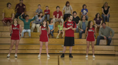 Cheerleader Skips in Front of Audience Stock Footage