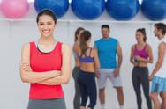 Stock Photo of Smiling woman with friends in background at fitness studio
