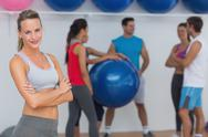 Stock Photo of Fit young woman with friends in background at fitness studio
