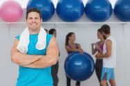Stock Photo of Smiling man with friends in background at fitness studio