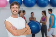 Stock Photo of Man with friends in background at fitness studio
