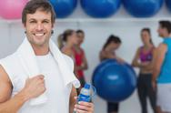 Stock Photo of Man holding water bottle with friends in background at fitness studio