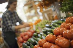 organic farmer at work. a young man arranging a display of fresh produce on a - stock photo
