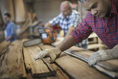 A reclaimed lumber workshop. a group of people working. a man measuring and c Stock Photos