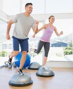 Couple doing step aerobics in fitness studio Stock Photos