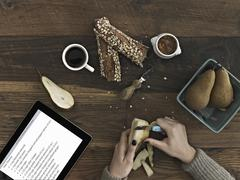 a person using a peeling knife to peel a pear. a computer tablet device with  - stock photo