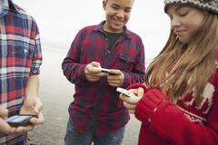 a day out at ashokan lake. teenagers, a girl and two boys texting and looking - stock photo