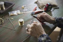 A tabletop with jewellery making equipment. hands twisting wire on a necklace Stock Photos