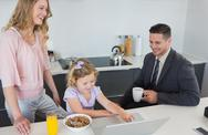 Stock Photo of Parents with daughter using laptop during breakfast time