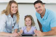 Stock Photo of Parents and cute girl using digital tablet