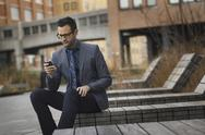 Stock Photo of a man in a formal jacket and tie, sitting on a bench outside a city building,