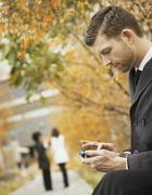 City life. a man in the park checking and texting, keeping in contact, using  Stock Photos