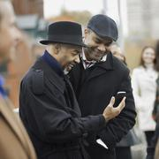 City life. two men standing side by side, keeping in contact, using mobile ph Stock Photos