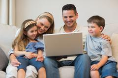 Family using laptop together on sofa - stock photo