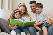 Stock Photo of Family watching photo album on sofa