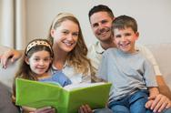 Stock Photo of Family with photo album sitting on sofa
