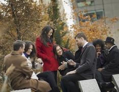 city life. a group of people on the go, keeping in contact, using mobile phon - stock photo