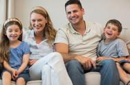 Stock Photo of Happy parents and children sitting on sofa