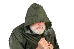 Pathetic senior bearded man in green waterproof jacket Stock Photos