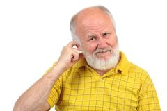 Bald senior man picking his ear with index finger Stock Photos