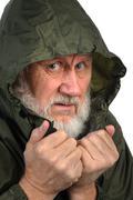 Pathetic senior man in green waterproof hoody Stock Photos