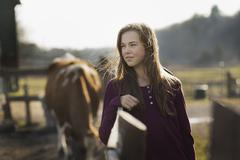 a girl leaning on a paddock fence, and a grazing horse in the background, on  - stock photo