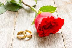 Stock Photo of two golden rings and red rose