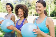 Stock Photo of Happy women exercising with medicine balls