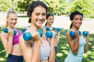 Stock Photo of Happy multiethnic women lifting dumbbells