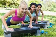 Stock Photo of Sporty women doing step aerobics