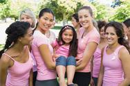 Stock Photo of Women carrying girl during breast cancer awareness