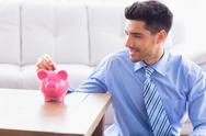Stock Photo of Smiling businessman putting coins into piggy bank