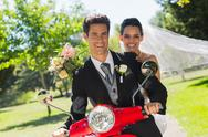 Stock Photo of Newlywed couple sitting on scooter in park