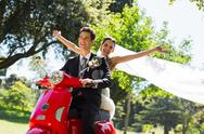 Stock Photo of Newlywed couple enjoying scooter ride