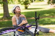 Stock Photo of Female bicyclist with hurt leg sitting in park