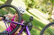 Stock Photo of Woman trying to fix chain on mountain bike in park