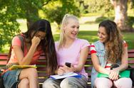Stock Photo of Happy female college friends sitting on campus bench