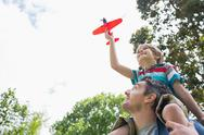 Stock Photo of Boy with toy aeroplane sitting on father's shoulders