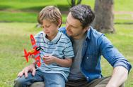 Stock Photo of Boy with toy aeroplane sitting on father's lap