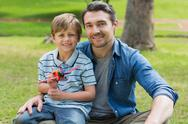 Stock Photo of Boy with toy aeroplane sitting on father's lap at park
