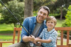 Father and son fishing on park bench - stock photo