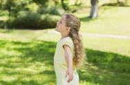 Stock Photo of Girl with arms outstretched looking upwards at park